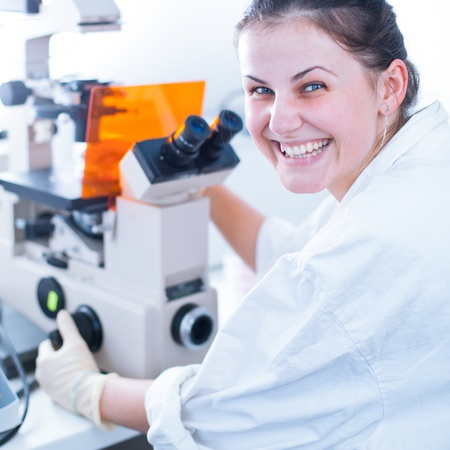 portrait of a female researcher doing research in lab using microscope (color toned image; shallow DOF) photo