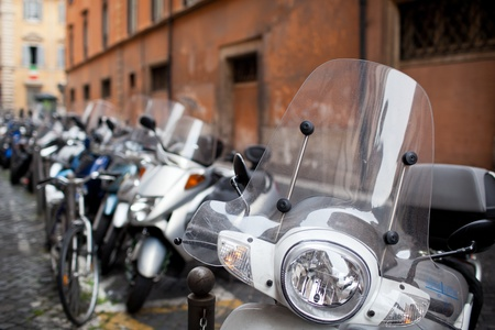 motor bike: Row of motorbikes and scooters parked in one of the ancient streets of Rome