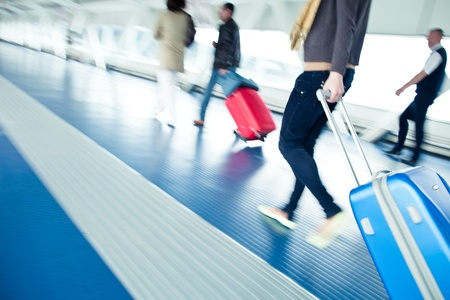 business traveller: Airport rush  people with their suitcases walking along a corridor  motion blurred image; color toned image  Stock Photo