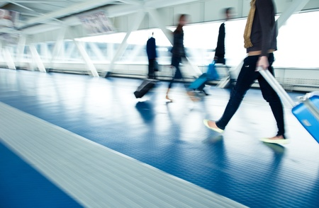 Airport rush  people with their suitcases walking along a corridor  motion blurred image; color toned image  photo