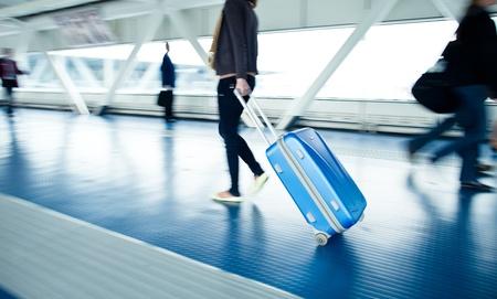 gente aeropuerto: Aeropuerto de punta: la gente con sus maletas caminando por un pasillo (imagen en movimiento borrosa, color de la imagen tono) Editorial
