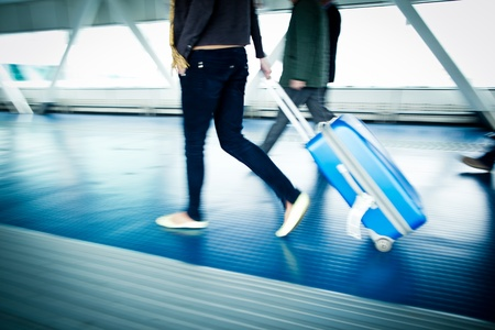 Airport rush  people with their suitcases walking along a corridor  motion blurred image; color toned image Stock Photo - 12653807