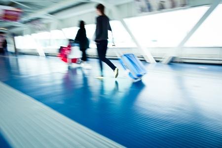 gente aeropuerto: Personas acometidas aeropuerto con sus maletas a pie a lo largo de un corredor de movimiento borrosa imagen, imagen en color entonado Foto de archivo