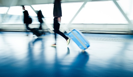 Airport rush: people with their suitcases walking along a corridor (motion blurred image; color toned image) photo