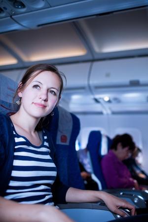 Bastante joven pasajera a bordo de un avión de imagen en color entonado