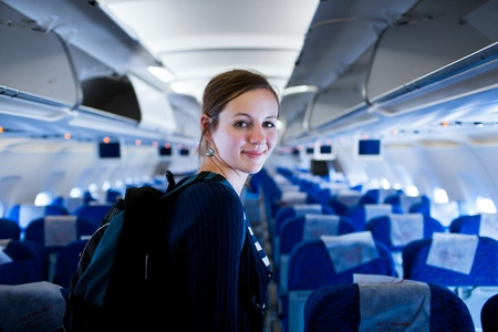 airline hostess: Pretty young female passenger on board of an aircraft  color toned image