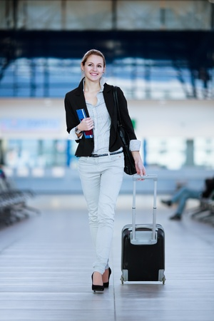 mujer con maleta: Bastante joven mujer de pasajeros en el aeropuerto (DOF, imagen en color entonado) Foto de archivo