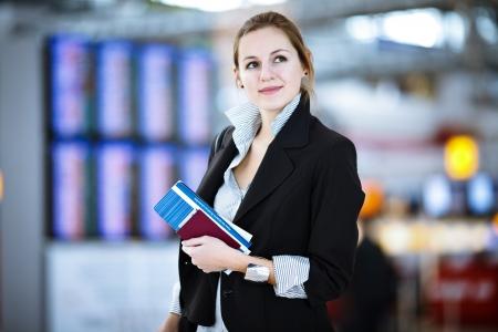 Mooie jonge vrouwelijke passagier op de luchthaven (ondiepe DOF, kleur getinte afbeelding)