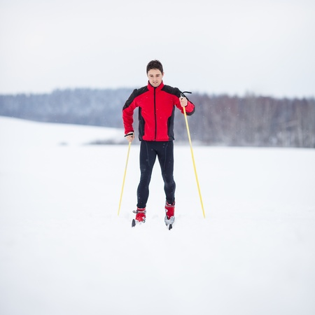 Cross-country skiing: young man cross-country skiing on a lovely snowy winter day photo