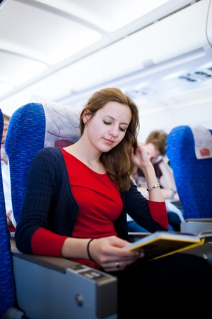 airline hostess: Pretty young female passenger on board of an aircraft, reading a travel guide while on the flight  color toned image  Stock Photo