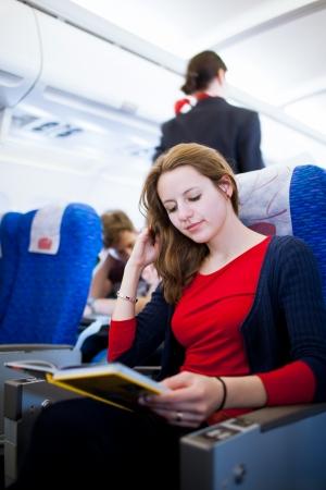 air hostess: Jolie jeune passag�re � bord d'un a�ronef, la lecture d'un guide de voyage sur l'image tout en couleur tonique vol Banque d'images