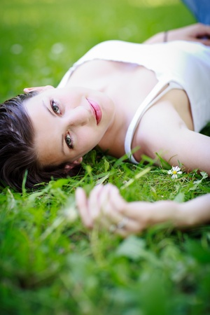 seductive women: Close-up portrait of an attractive young woman outdoors, lying in the grass, relaxing
