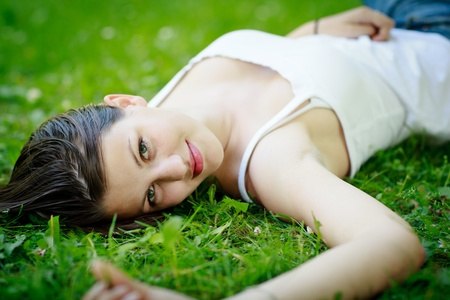 Close-up portrait of an attractive young woman outdoors, lying in the grass, relaxing photo