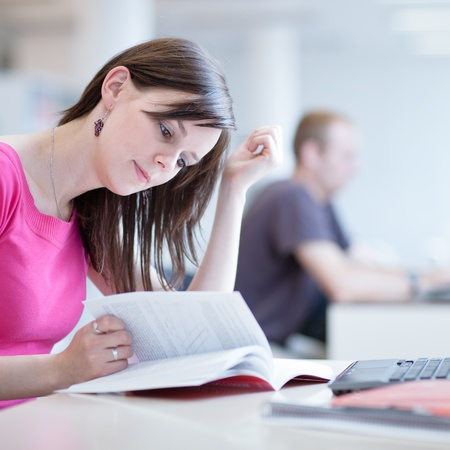 in the library - pretty female student with laptop and books working in a high school library Stock Photo - 12637069