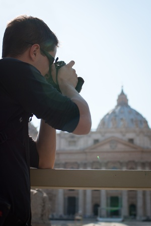 st  peter's square: Handsome young male tourist taking photos at St. Peters Square in Vatican (St. Peters Basilica in the background) Stock Photo