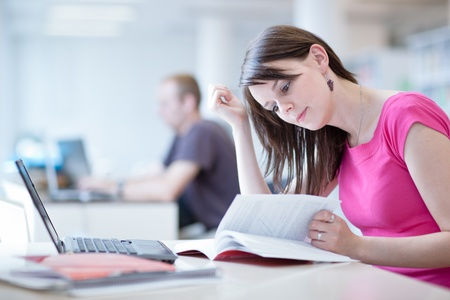 mature student: in the library - pretty female student with laptop and books working in a high school library   color toned image  Stock Photo