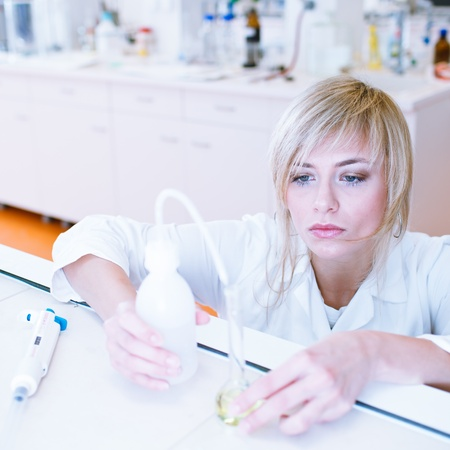 Closeup of a female researcherchemistry student carrying out experiments in a lab (color toned image) photo