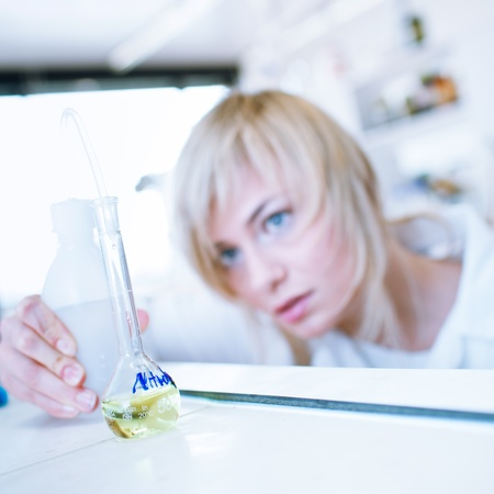 Closeup of a female researcher/chemistry student carrying out experiments in a lab (color toned image) Stock Photo - 12636926