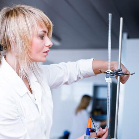 Closeup of a female researcherchemistry student carrying out experiments in a lab  photo
