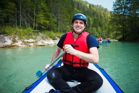 persevere: white water rafting - young man in a raft boat,  paddling, smiling Stock Photo