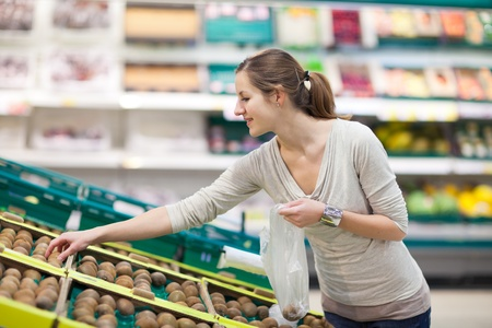 Beautiful youn woman shopping for fruits and vegetables in produce department of a grocery store/supermarket Stock Photo - 12637951