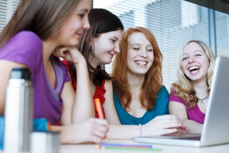 Three female college students working on their homeworkhaving a chat in between the lectures  photo