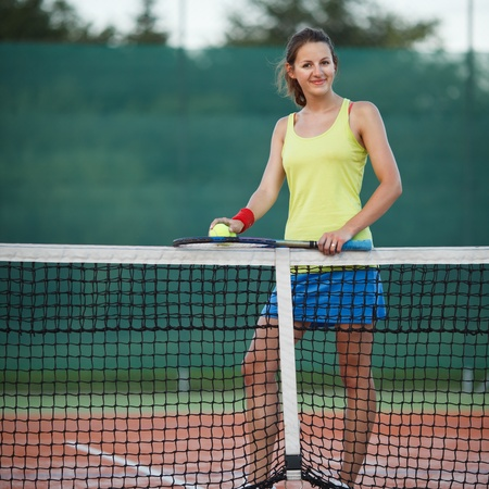 pretty, young female tennis player on the tennis court  shallow DOF, selective focus  photo