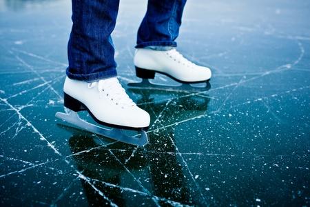 patinaje sobre hielo: Mujer joven de patinaje sobre hielo al aire libre en un estanque en un día helado de invierno - detalle de las piernas