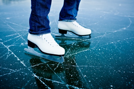 ice skating: Young woman ice skating outdoors on a pond on a freezing winter day - detail of the legs Stock Photo