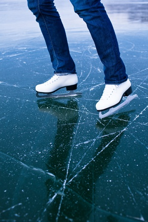 Young woman ice skating outdoors on a pond on a freezing winter day - detail of the legs Stock Photo - 12808946