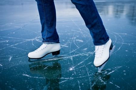 patinaje sobre hielo: Mujer joven de patinaje sobre hielo al aire libre en un estanque en un día helado de invierno - el detalle de las piernas