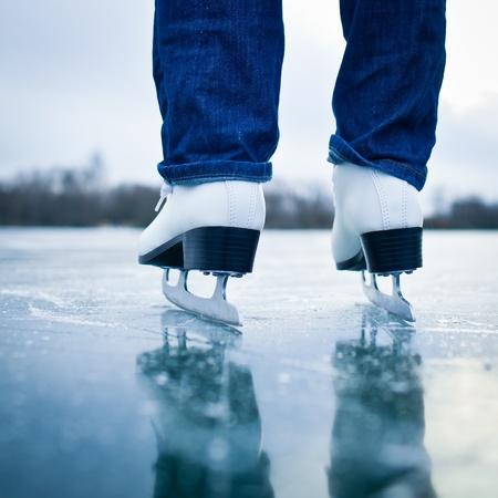 patinaje: Mujer joven de patinaje sobre hielo al aire libre en un estanque en un día helado de invierno - detalle de las piernas