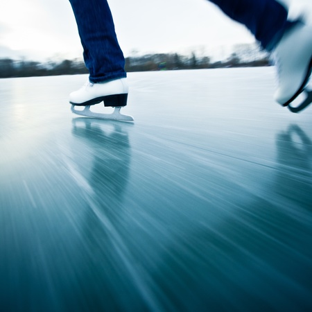patinaje: Mujer joven de patinaje sobre hielo al aire libre en un estanque en un d�a helado de invierno - el detalle de las piernas (desenfoque de movimiento se utiliza para transmitir la velocidad)