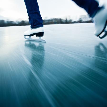 Jeune femme de glace à l'extérieur de patinage sur un étang sur un jour d'hiver de congélation - détail des jambes (flou de mouvement est utilisée pour transmettre la vitesse)