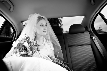 Portrait of a beautiful young bride waiting in the car on her way to the wedding ceremony photo