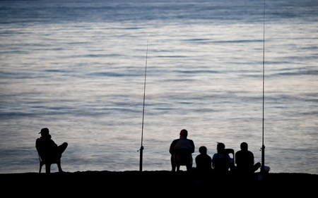 Sea/Ocean fishing - fishermen sitting by the sea/ocean in darkness waiting for the catch Stock Photo - 12808403