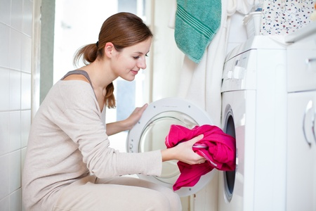 Housework: young woman doing laundry (shallow DOF; color toned image) photo