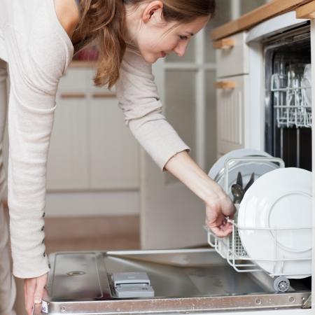 geschirrsp�ler: Hausarbeit: junge Frau Putting Geschirr in der Sp�lmaschine Lizenzfreie Bilder