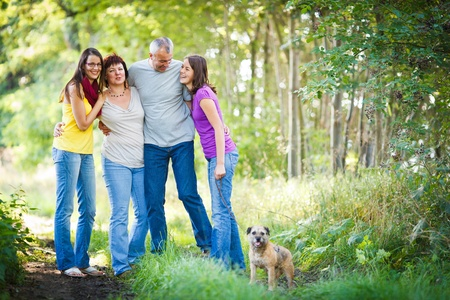 thirties portrait: Family portrait - Family of four with a cute dog outdoors