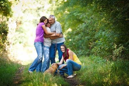 familia unida: Retrato de familia - la familia de cuatro con un lindo perro al aire libre Foto de archivo