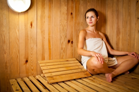 sauna: Young woman relaxing in a sauna