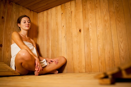 Young woman relaxing in a sauna Stock Photo - 12989727