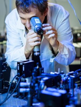 experimento: cient�fico que hace investigaci�n en un laboratorio de �ptica cu�ntica DOF someras, la imagen tonos de color Foto de archivo