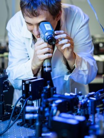 scientist doing research in a quantum optics  lab  shallow DOF; color toned image  photo