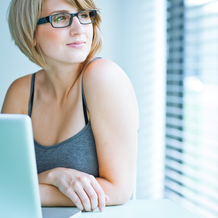 woman wearing glasses: Portrait of a young woman pensively looking out of the window while sitting in front of her laptop