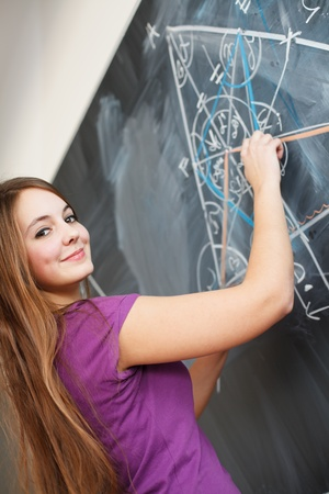 pretty young college student writing on the chalkboard blackboard during a math class  color toned image; shallow DOF  photo