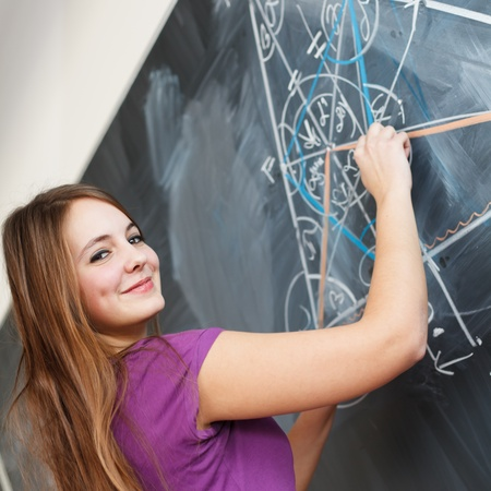 pretty young college student writing on the chalkboardblackboard during a math class (color toned image; shallow DOF) photo