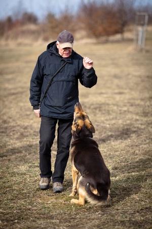 obediencia: Maestro y su obediente perro de pastor alemán Foto de archivo