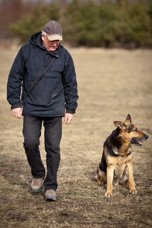 shepherd's companion: Master and his obedient  German Shepherd  dog Stock Photo