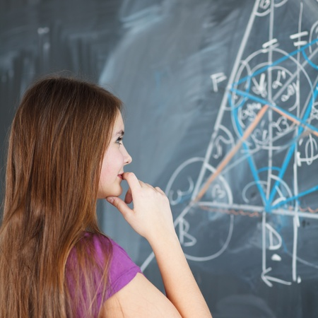 pretty young college student writing on the chalkboard blackboard during a math class  color toned image; shallow DOF  Stock Photo - 13153785